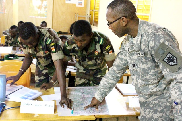 Nigerien army Lts Ismaila Abdou Hamza, Nigerien army Lt. Aboubacar Anadon and U.S. Army Capt. Dominique Louis plot targets for analysis during their basic map-reading course in Niamey, Niger, Oct. 28, 2015.