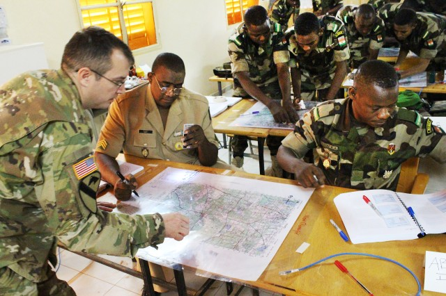 U.S. Army Maj. Jeremy Gettig, Nigerien army Staff Sgt. Moussa Oumarou Baoua and Nigerien army Lt. Amouzou K. Anani plot targets for analysis during their basic map-reading course in Niamey, Niger, Oct. 28, 2015.