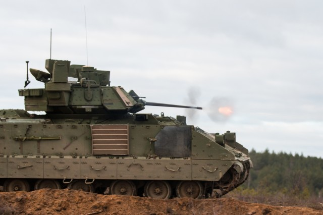 A Bradley Fighting Vehicle, belonging to the 3rd Battalion, 69th Armor Regiment, 1st Armor Brigade Combat Team, 3rd Infantry Division, engages targets during gunnery training at Pabrade Training Area, Lithuania, Dec. 2, 2015.