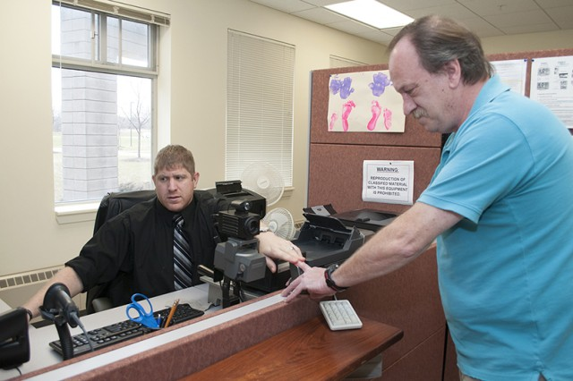 Michael Habermann, a Department of Army Civilian, obtains digital fingerprints from Chris MacGregor at the Fort Drum DEERS / ID Card office on Monday. The digital fingerprints are part of a secondary identification process.