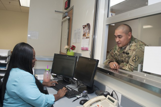 Shevon Henfield, a contract employee with Fort Drum DEERS / ID Card office, greets a customer at the reception window on Monday.