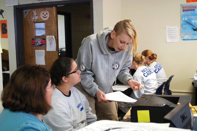JANNA JESSON, AN AMERICORPS NATIONAL CIVILIAN COMMUNITY CORPS MEMBER, reads over a writing assignment from Tori Burton of Somerset, Kentucky. With her background in English and communication, Jesson helps tutor students in writing and grammar.