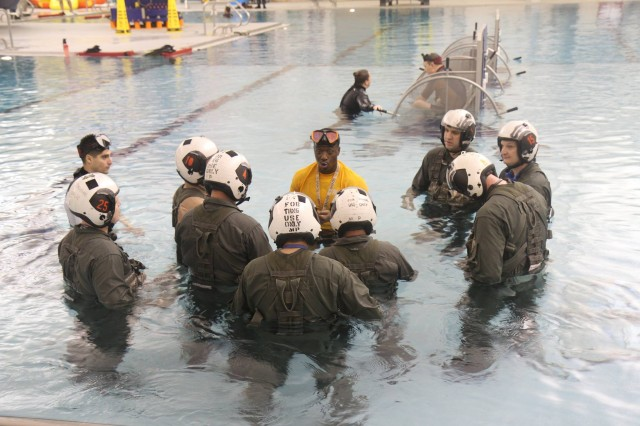 U.S. AH-64E Apache pilots assigned to 16th Combat Aviation Brigade receive instruction during water survival training at Naval Air Station Whidbey Island, Washington, Dec. 2, 2015. This training prepares pilots to handle emergencies in any environment.