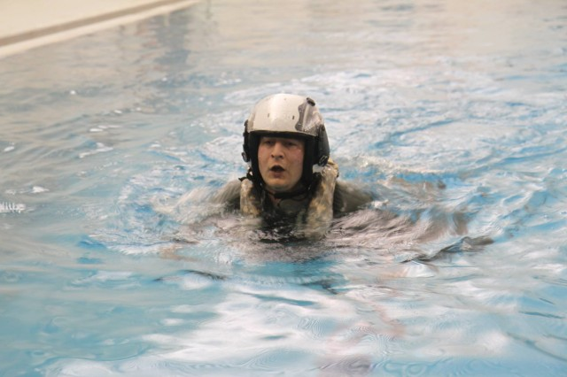 A U.S. Army AH-64E Apache pilot assigned to 16th Combat Aviation Brigade practices swimming in flight gear during water survival training at Naval Air Station Whidbey Island, Washington, Dec. 2, 2015. This training prepares pilots to handle emergencies in any environment.