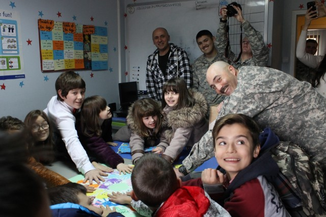 U.S Army Maj. Jamie Bowen, the senior operations officer for the 30th Armored Brigade Combat Team and Multinational Battle Group-East headquarters, joins A&A Learning Center students in touching handprints painted by U.S. students from Saint Francis de Sales Catholic School in Beckley, W.V., during a Nov. 23, 2015, visit to the learning center in Pristina, Kosovo. The handprints were given to the A&A Learning Center along with donated school supplies delivered by Soldiers assigned to MNBG-E, who visited the school as part of a community outreach effort that included practicing language skills and joining the children on a trip to Pristina's Bear Sanctuary. (U.S. Army photo by Sgt. Erick Yates, Multinational Battle Group-East)