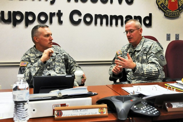 Col. Dale Kuehl, left, Chief of Staff, First Army, speaks with Army Reserve Col. Robert Rauchle, Deputy Commanding Officer, 85th Support Command, during a break at the First Army brigade executive officers brief, Dec. 4. The purpose of the briefing was to assist the active component brigades better understand the different processes within their Army Reserve battalions, and improve communications between the active and reserve units assigned to the brigades. (U.S. Army photo by Spc. David Lietz/Released)