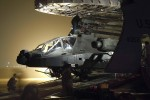 Theater Aviation Sustainment and Maintenance Group Soldiers offload an AH-64 Apache helicopter from a C-5 Galaxy aircraft during a night mission at an aerial port of debarkation.
