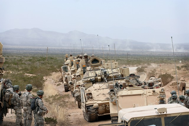 Bradley fighting vehicles move forward to a refuel on the move site on March 30, 2015, during the 1st Armored Division's exercise Iron Focus 15 at Fort Bliss, Texas.