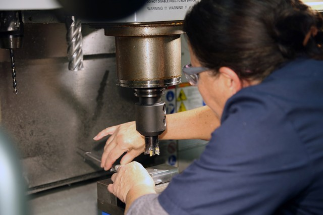 Hortansia Zaccheus, an Advanced Leader Course instructor for allied trades specialists at the Army Logistics University, checks a measurement before manually making a cut with a computer numerical control toolroom mill during train-the-trainer instruction at the Ordnance School at Fort Lee, Virginia.