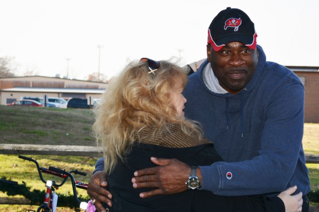 Susan Garling, a Holiday Helper Association board member, embraces Sgt. 1st Class Willie Nelson III as a thank you gesture after the Army Reserve Soldier, who's also The Army School System Training Center, Fort Lee noncommissioned officer in charge, and 23 students enrolled the 94th Training Division's Quartermaster Senior Leadership Course took time out of their grueling 17-week class schedule to help the nonprofit Holiday Helper Association Toy Store prepare for the holidays. The students assembled 30 toy bicycles in an hour, and they also helped beautify and organize the all-volunteer run facility in preparation of the association's annual open house, scheduled for Dec. 11, and two Christmas shopping days scheduled for Dec. 15 and 16, 2015.