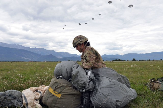 First Lt. Kristina-Noel N. Donohue, aerial delivery officer, 173rd Brigade Support Battalion, 173rd Airborne Brigade, begins to recover her parachute after an airborne operation from a U.S. Air Force 86th Air Wing C-130 Hercules aircraft at Juliet Drop Zone in Pordenone, Italy, Dec. 2, 2015. The 173rd Airborne Brigade is the U.S. Army Contingency Response Force in Europe, capable of projecting ready forces anywhere in the U.S. European, Africa or Central Commands' areas of responsibility within 18 hours. (U.S. Army Photos by Visual Information Specialist Paolo Bovo/Released)
