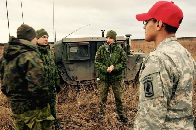U.S. and Lithuanian soldiers converse during Operation Iron Sword in Lithuania, Nov. 18, 2015.