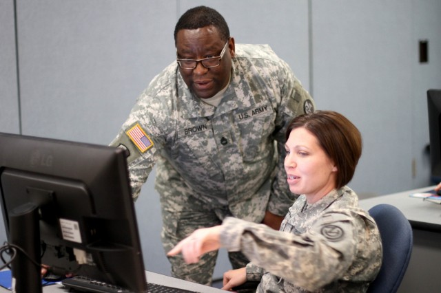Instructor Sgt. 1st Class Rick D. Brown, assigned to the 8/98th Regiment, Fort Dix, N.J., assists Sgt. Marcy DiOssi, of the 1/95th Engineer Battalion out of Fort Leonard Wood, Mo., with the preparation of her class presentation.