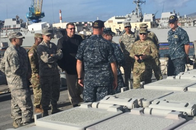 Harry Hallock, (center in the dark jacket) deputy assistant secretary of the Army for Procurement, receives a briefing from U.S. Navy Lt. Andy Bell and Lt. j.g. Mike Brow on the USS Paul Hamilton, a Navy destroyer at Joint Base Pearl Harbor-Hickam, Hawaii. The senior contracting leaders spent seven days in Oahu visiting commands across the island