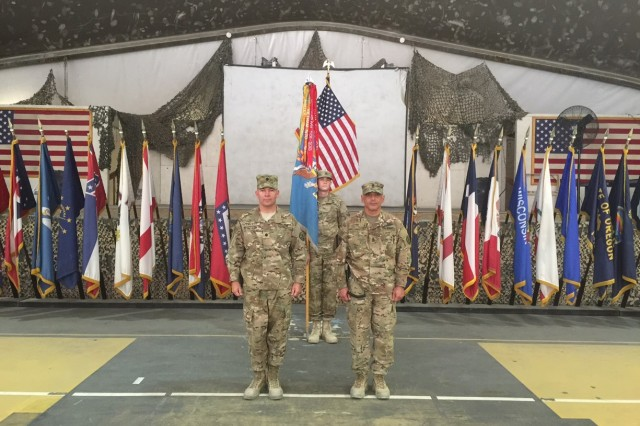 Lt. Col. AJ Covert (left) and Command Sgt. Maj. Gregory Camacho-Vera (right) stand at attention after uncasing the 303rd MI Battalion's colors during a ceremony in Afghanistan. The battalion is comprised of human intelligence, signals intelligence, geospatial intelligence, and counterintelligence Soldiers who support U.S. and coalition forces in Afghanistan.