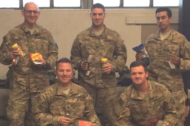 Capt. Chad Lorenz (back center), commander of B Company, 303rd Military Intelligence Battalion, 504th Military Intelligence Brigade, stands with members of his company who received care package items in a recent holiday care package.