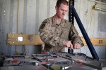 Spc. James Bowman charges batteries that will be issued to various units in Afghanistan on Aug. 7, 2014.