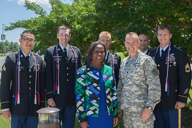 Retired Command Sgt. Maj. Althea Green-Dixon, front, director of the Enlisted to Medical Degree Preparatory Program at the Uniformed Services University of the Health Sciences, and Command Sgt. Maj. Gerald Ecker of Army Medical Command pose with Sgt. Steven Capen, Staff Sgt. Claude Blereau, Sgt. 1st Class Steven Radloff, Sgt. 1st Class Jesus Villarreal and Sgt. 1st Class Joshua Richter.
