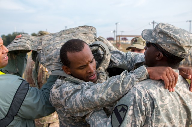"Sgt. Justyn Duke (center), a geospatial engineer with Headquarters and Headquarters Company, 1st Armored Brigade Combat Team, 1st Cavalry Division, has his Improved Outer Tactical Vest taken off of him as he finishes the 100 m ""burpee"" broad jump during the Iron Hammer Challenge Dec. 10 at Fort Hood, Texas. The competition brought together Soldiers from many different occupational specialties and ranks. (U.S. Army photo by Sgt. Christopher Dennis, 1st Armored Brigade Combat Team Public Affairs, 1st Cav. Div.)"