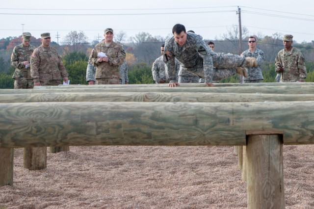 Sgt. Patrick Maurer, a cavalry scout with HHC, 1st ABCT, 1st Cav. Div., tackles the log hurdles during the Iron Hammer Challenge Dec. 10 at Fort Hood, Texas. (U.S. Army photo by Sgt. Christopher Dennis, 1st Armored Brigade Combat Team Public Affairs, 1st Cav. Div.)