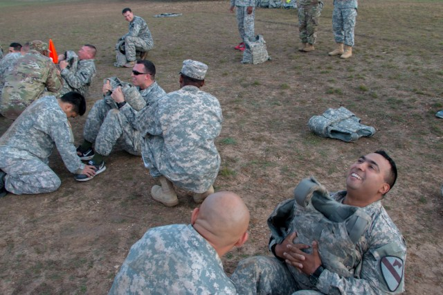 Soldiers from Headquarters and Headquarters Company, 1st Armored Brigade Combat Team, 1st Cavalry Division, knock out sit-ups with the extra weight of their Improved Outer Tactical Vests as a part of the Iron Hammer Challenge Dec. 10 at Fort Hood, Texas. (U.S. Army photo by Sgt. Christopher Dennis, 1st Armored Brigade Combat Team Public Affairs, 1st Cav. Div.)