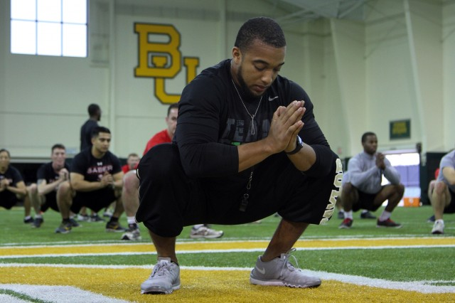 Coach Tony Randolph, Baylor University Associate Director of Athletic Performance for Football, demonstrates stretching techniques used by the football team before practice to Soldiers of 91st Engineer Battalion, 1st Armored Brigade Combat Team, 1st Cavalry Division. The stretching demonstration was part of a two-day seminar hosted by Baylor to teach different training techniques to Army physical fitness trainers and commanders. (U.S. Army photo by Sgt. Fred Brown, 1st Armored Brigade Combat Team Public Affairs, 1st Cav. Div.)