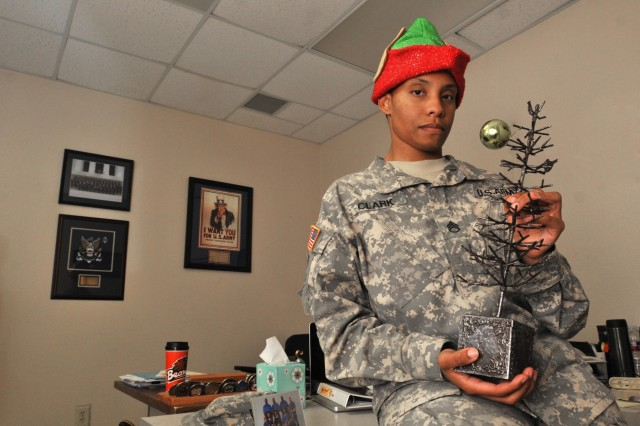 Staff Sgt. Tomora Clark holds her scantly decorated Christmas tree at the 3rd Cavalry Regiment headquarters building Dec.15 at Fort Hood, Texas. Will she find time to accomplish all of her holiday chores last minute? (Photo by Spc. Erik Warren, 3rd Cavalry Regiment Public Affairs)