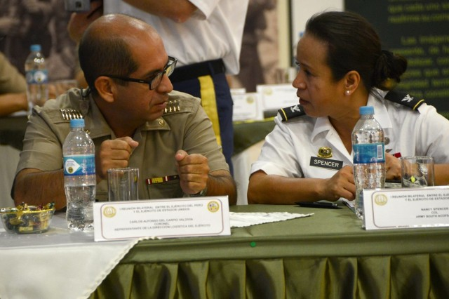 Col. Nancy Spencer, U.S. Army South director of logistics, speaks with Peruvian Col. Carlos Alfonso del Carpio Valdivia, of Peruvian army logistics, before the opening ceremony of the inaugural bilateral army-to-army staff talks between the U.S. Army and the Peruvian army in Lima, Peru, Dec. 14, 2015.