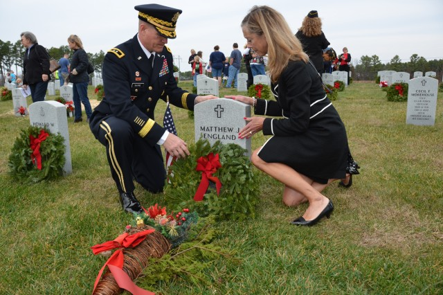 Maj. Gen. Kent Savre, Fort Leonard Wood and Maneuver Support Center of Excellence commanding general, and his wife, Mary Beth, place a wreath on Pfc. Matthew England's grave Saturday at the Missouri Veterans Cemetery in Waynesville.