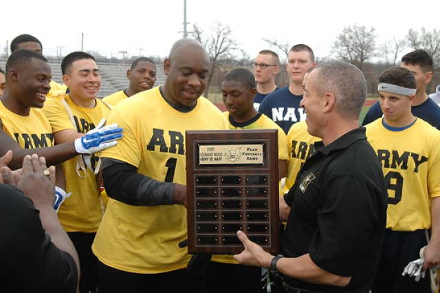 Army quarterback Horace Gibson accepts the winner's plaque from Col. Andy Herbst, U.S. Army Garrison Fort Leonard Wood commander, following the Army team's victory Saturday.