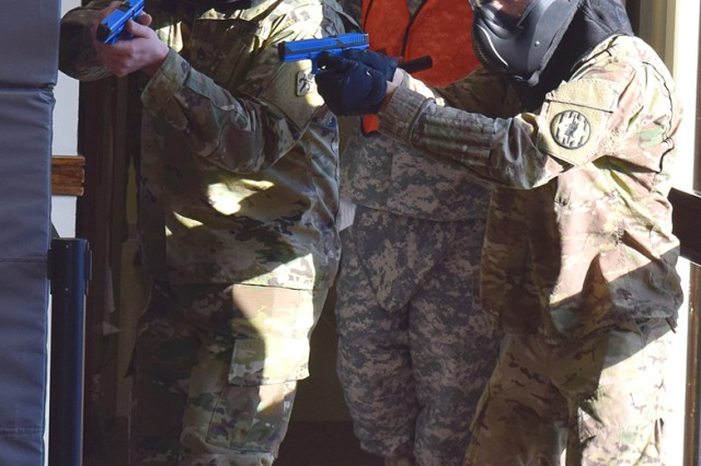 Two participants in the five-day Advanced Law Enforcement Rapid Response Training course prepare to engage a role-player in a training scenario at the Military Police Training Division Law Enforcement Academy, Dec. 10, 2015.