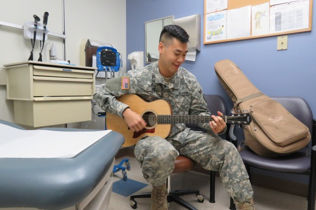 Capt. Edwin Choi, a family medicine resident, plays his guitar on occasion to comfort patients.
