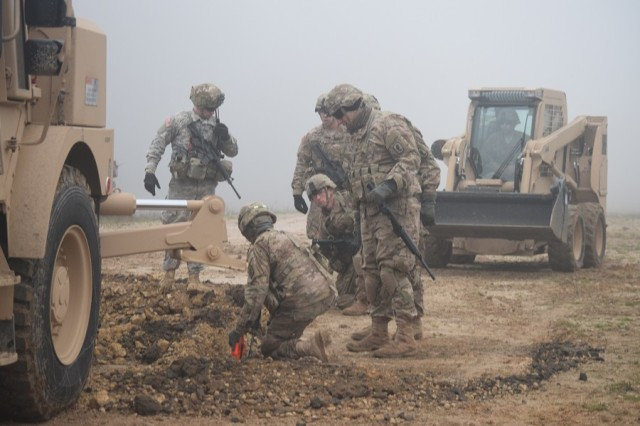 Equipment operators from A and B Co, 54th BEB (A) analyze a crater near the flight landing strip to practice filling it in. Crater repair is a key task for airfield repair and enabling air operations on a seized airfield.