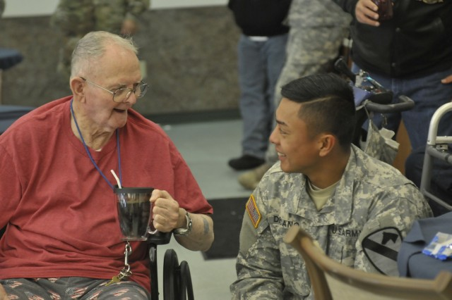 Sgt. Guian Decano, right, a Haymaker, Va., native, and the squadron ammunition noncommissioned officer in charge with the 6th Squadron, 9th Cavalry Regiment, 3rd Armored Brigade Combat Team, 1st Cavalry Division, talks to a veteran, left, at the William R. Courtney Texas State Veterans Home in Temple, Texas, Dec. 18, 2015.