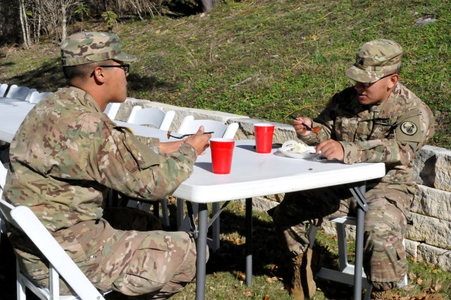 Sgt. Carlos Hernandez (right), a native of Brownsville, Texas, and Spc. Kevyn Tak, left, originally from Snellville, Ga., both assigned to the 518th Sustainment Brigade, eat a barbeque lunch provided by Gatesville, Texas, residents and volunteers at the Peacock River Ranch in Gatesville Dec. 17. The event provided members of the North Carolina-based unit a Christmas party while they are away from home training with the 120th Infantry Brigade for an upcoming deployment. (Photo by Sgt. 1st Class Thomas Wheeler, Division West Public Affairs)