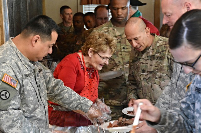 Loretta Elledge (center), a resident of Gatesville, Texas, serves food to Soldiers assigned to the 518th Sustainment Brigade during a holiday party held at the Peacock River Ranch in Gatesville Dec. 17. The event was sponsored by Gatesville residents for the North Carolina-based unit training with the 120th Infantry Brigade at North Fort Hood for an upcoming deployment. First Army Division West is partnered with the Gatesville community as part of the Fort Hood Community Partnership Program. (Photo by Sgt. 1st Class Thomas Wheeler, Division West Public Affairs)