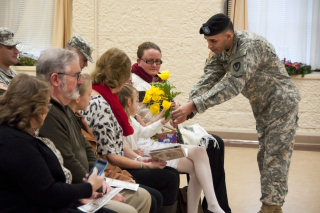 Staff Sgt. Joel Ramirez, Headquarters and Headquarters Company, U.S. Army Sustainment Command, hands flowers to the family of Capt. Michael Rear, commander, HHC ASC, during a change of command ceremony in Heritage Hall, Rock Island Arsenal, Illinois, Dec 21. (Photo by Kevin Fleming, ASC Public Affairs)