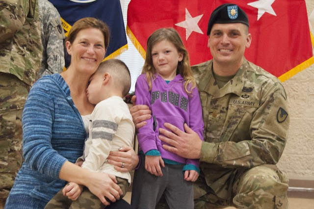 Maj. Chandler Fisk, outgoing commander, Headquarters and Headquarters Company, U.S. Army Sustainment Command, gathers with his family following the HHC change of command ceremony in Heritage Hall, Rock Island Arsenal, Illinois, Dec 21. (Photo by Kevin Fleming, ASC Public Affairs)
