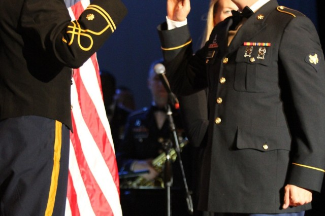 "Spc. Francis Franqui (right), a trumpet player with the 1st Cavalry Division Band, reenlists prior to the start of the band's ""A Hill Country Holiday"" concert Dec. 17 at the Harker Heights High School auditorium in Harker Heights, Texas. (U.S. Army photo by Staff Sgt. Christopher Calvert, 1st Cavalry Division PAO (Released))"