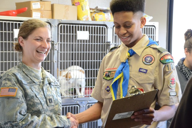 Captain Emily Farmer, Fort Campbell Veterinary Clinic, receives a shipment of new cat beds, pet food bowls and toys from 16-year-old Boy Scout Eric Merritt Tuesday. Farmer said the interactive items will help the animals to socialize in the stray facility and become better pets for adoptive Families.