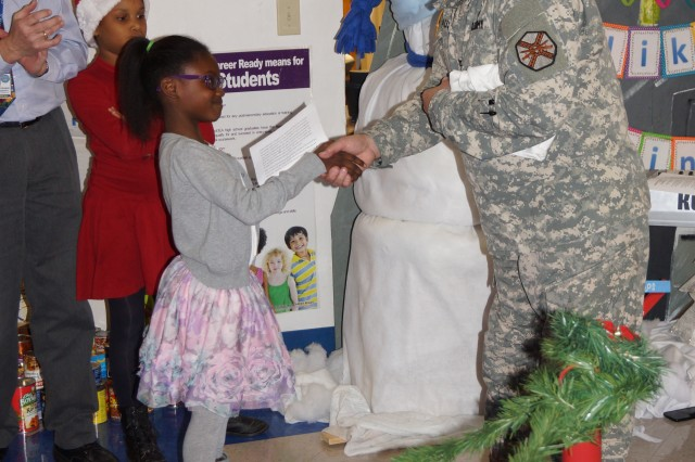 Syann Bradley, a member of Lincoln Elementary School's third grade student council, presents Col. Terry Austin, the Fort Campbell garrison chaplain, with the 680 food items students donated during a food drive Thursday at Fort Campbell. Bradley also gave Austin a school shirt when she made him an honorary member of the school.