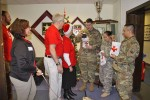 Spc. Charles Smith, Staff Sgt. Yolisma Cisneros and Spc. Marc Lopez, receive surprise packages from Kimberly Chromicz, assistant station manager for the local Red Cross and several Red Cross volunteers.  The three Soldiers were working at the Baumholder Installation Duty Office on Christmas Day. The gift packages were donated by Amazon and included several goodies and an Amazon Fire HD6 tablet.