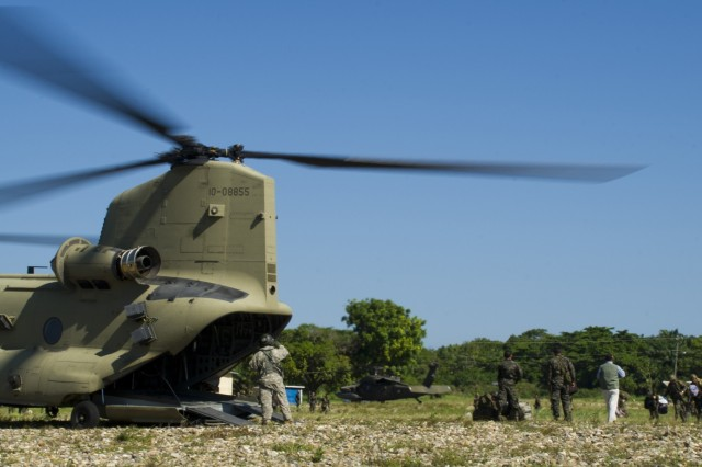 U.S. Army Sgt. David Pressnell, 1-228th Aviation Regiment flight engineer, directs Honduran soldiers loading gear and personnel into the back of a U.S. Army CH-47 Chinook, Dec. 16, 2015, in the Gracias a Dios Department (state) of Honduras during a troop movement the U.S. provides support to.