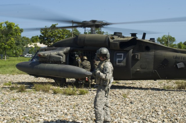 U.S. Army Cpl. Brain McKee, 1-228th Aviation Regiment flight engineer, helps Honduran troops load into a U.S. Army UH-60 Black Hawk helicopter with their gear, Dec. 16, 2015, in the Gracias a Dios Department (state) of Honduras.