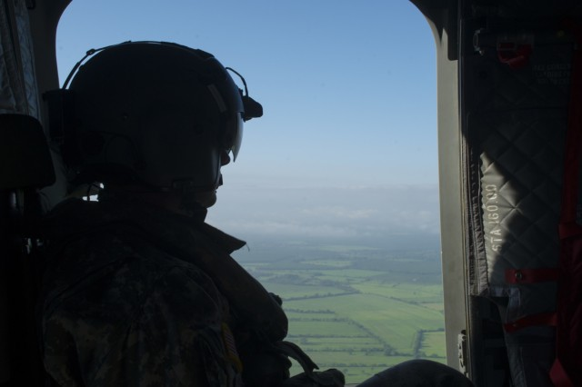 David Uplinger, 1-228th Aviation Regiment flight engineer, watches the landscape slip by the door of a U.S. Army CH-47 Chinook, Dec. 17, 2015, as the aircraft flies over the Gracias a Dios Department (state) of Honduras.