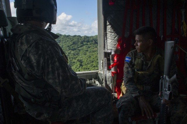 David Uplinger, 1-228th Aviation Regiment flight engineer, and a Honduran troop watch the trees slip by the door of a U.S. Army CH-47 Chinook, Dec. 17, 2015, as they fly over the Gracias a Dios Department (state) of Honduras.