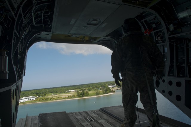U.S. Army Sgt. David Pressnell, 1-228th Aviation Regiment flight engineer, provides visual aid to his fellow U.S. Army CH-47 Chinook aircrew as the helicopter departs a Honduran base in the Gracias a Dios Department (state) of Honduras, Dec. 17, 2015.