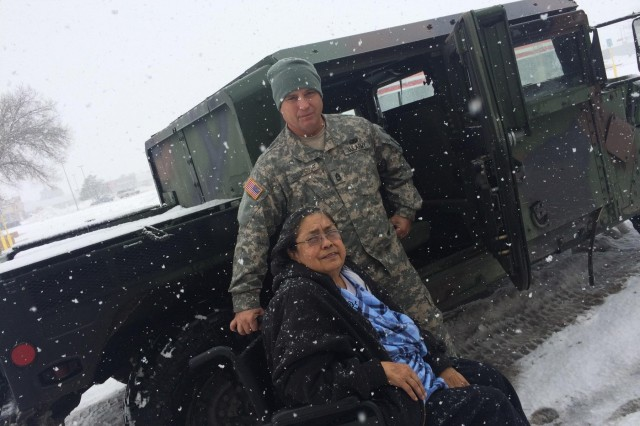 Sgt. 1st Class Christopher Vaillancourt, Headquarters and Headquarters Company, 717th Brigade Support Battalion, poses with a Roswell citizen he helped transport to the Fresenius Medical Care Center, Dec. 29, 2015.