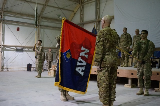 Spc. Kevin Palomera, a human resources specialist in the 40th Combat Aviation Brigade, or CAB, presents the brigade colors for Col. Jeffrey Holliday, commander of the 40th CAB, at the Transfer of Authority Ceremony with the 185th Theater Aviation Brigade at Camp Buehring, Kuwait, Dec. 20, 2015.