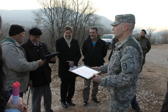 U.S. Army Col. Chris Selvey, deputy commander for Multinational Battle Group-East, hands certificates of appreciation to local landowners and leaders during a Dec. 21, 2015, ceremony returning land formerly used by the Kosovo Force to its civilian owners in Zupce, Kosovo.